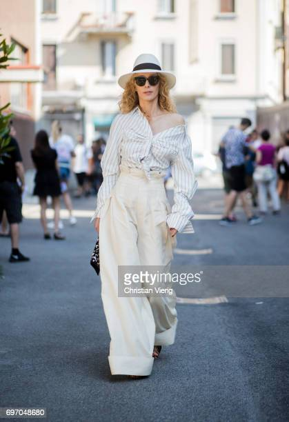 Elina Halimi wearing beige high waisted pants striped knotted button shirt hat is seen outside Diesel during Milan Men's Fashion Week Spring/Summer...