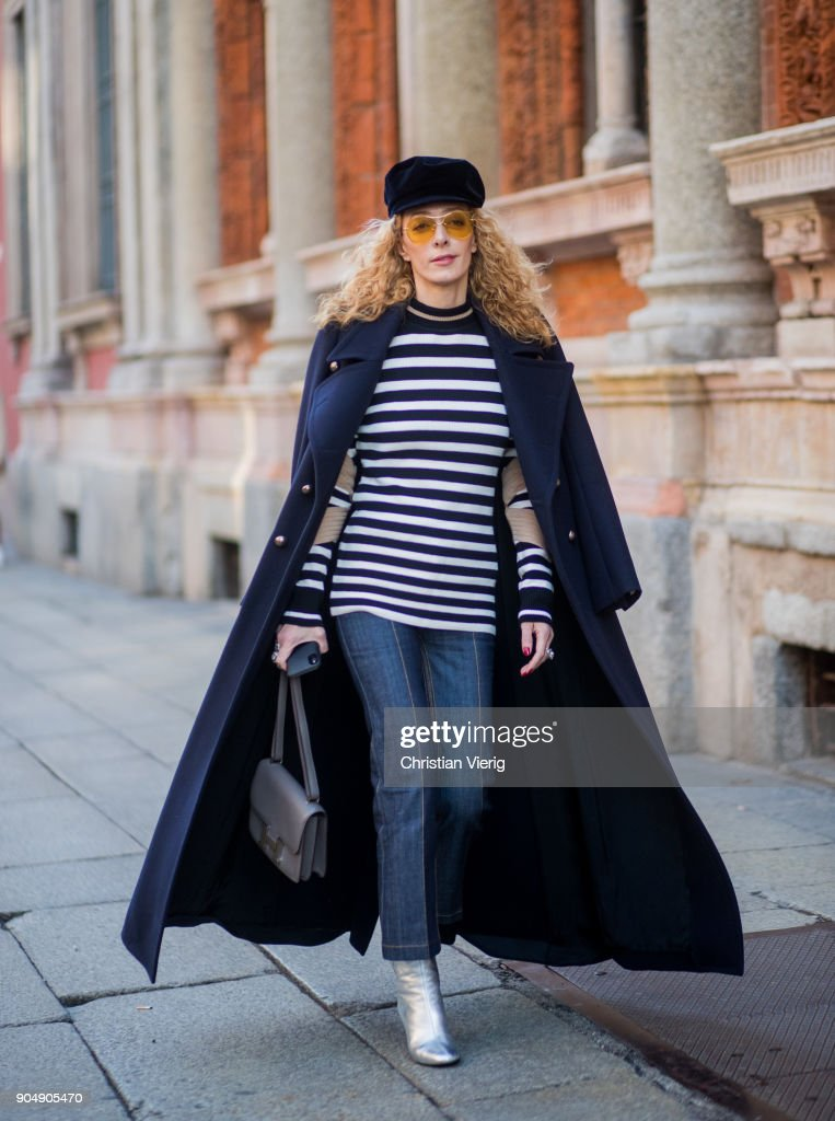 Elina Halimi wearing flat cap, striped top, coat, cropped denim jeans, silver boots is seen outside MSGM during Milan Men's Fashion Week Fall/Winter 2018/19 on January 14, 2018 in Milan, Italy.