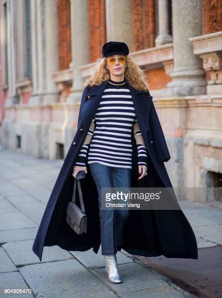 Elina Halimi wearing flat cap striped top coat cropped denim jeans silver boots is seen outside MSGM during Milan Men's Fashion Week Fall/Winter...
