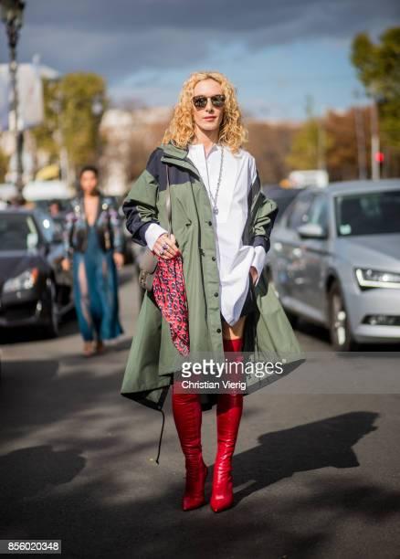 Elina Halimi wearing parka red overknee boots is seen outside Elie Saab during Paris Fashion Week Spring/Summer 2018 on September 30 2017 in Paris...