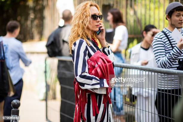Elina Halimi wearing red bag with fringes black white striped suit while calling on the phone is seen outside Y/PROJECT on day two of Paris Fashion...