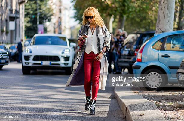 Elina Halimi wearing red pants trench coat and boots outside Marni during Milan Fashion Week Spring/Summer 2017 on September 25 2016 in Milan Italy