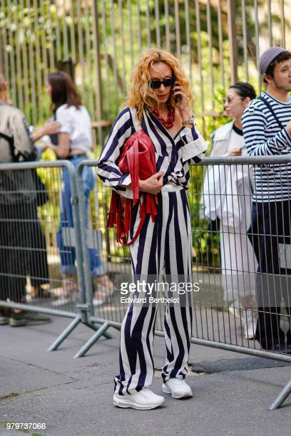 Elina Halimi wears a black and white striped outfit a red bag white sneakers outside Y/Project during Paris Fashion Week Menswear SpringSummer 2019...