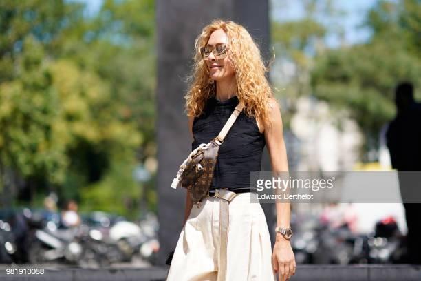 Elina Halimi wears a black tank top white flared pants a Vuitton bag outside Juun J during Paris Fashion Week Menswear SpringSummer 2019 on June 22...