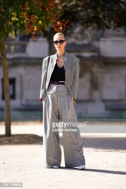 Elina Halimi wears a gray blazer jacket a black low neck top gray flare pants sunglasses outside Elie Saab during Paris Fashion Week Womenswear...