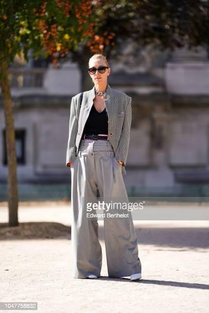 Elina Halimi wears a gray blazer jacket a black low neck top gray flare pants sunglasses outside Elie Saab during Paris Fashion Week Womenswear...