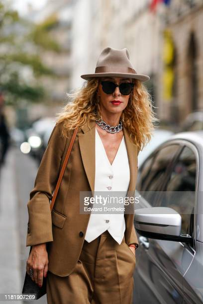 Elina Halimi wears a hat sunglasses red lipstick a bejewelled necklace a brown blazer jacket a white suit jacket flare pants outside Thom Browne...