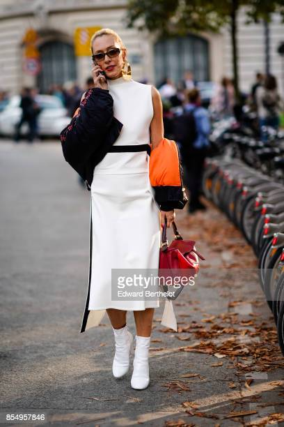 Elina Halimi wears a white dress white boots a red bag outside the Rochas show during Paris Fashion Week Womenswear Spring/Summer 2018 on September...
