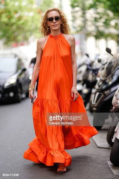 Elina Halimi wears an orange dress outside the Elie Saab show during Paris Fashion Week Haute Couture Fall/Winter 20172018 on July 5 2017 in Paris...