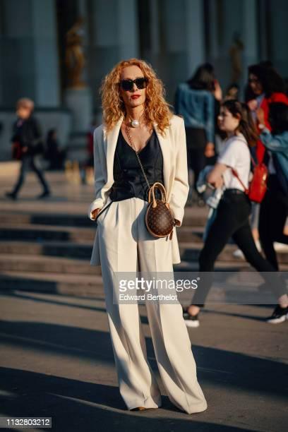 Elina Halimi wears sunglasses a big pearl necklace a black lowcut top a white pantsuit with wideleg fluid pants a Louis Vuitton monogram bag outside...