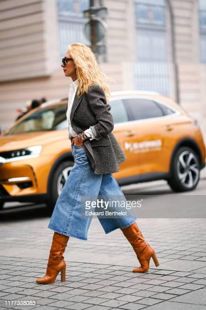 Elina Halimi wears sunglasses, a white shirt, a grey tweed jacket, blue denim wide-legs short pants, tan-color boots, outside Guy Laroche, next to a...