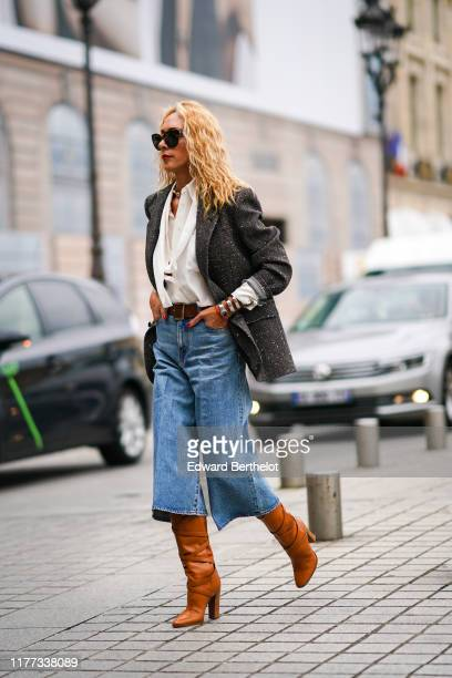 Elina Halimi wears sunglasses a white shirt with a lavaliere a grey tweed jacket a brown belt blue denim widelegs short pants tancolor boots outside...