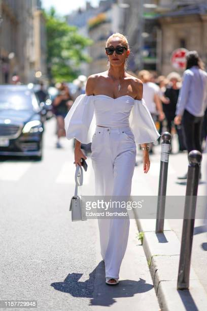 Elina Halimi wears sunglasses, an off-shoulder flared top, flared pants, a bag, outside Thom Browne, during Paris Fashion Week - Menswear...