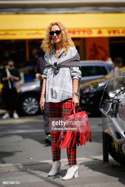 Elina Halimi wearsa shirt red tartan checked pants a red bag with fringes outside Issey Miyake during Paris Fashion Week Menswear SpringSummer 2019...