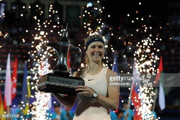 Elina Svitolina of Ukraine poses while holding the champion's trophy after winning the WTA Dubai Duty Free Tennis Championship on February 24, 2018....
