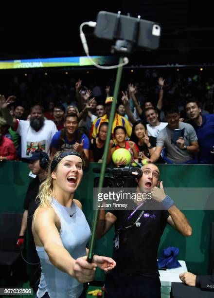 Elina Svitolina of Ukraine takes a selfie as she celebrates victory in her singles match against Simona Halep of Romania during day 6 of the BNP...