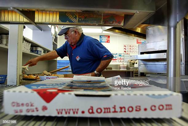 Elio Blanco cuts a Domino's Pizza April 14 2004 in Miami Florida Domino's Pizza is looking to raise $300 million in the stock market by listing on...