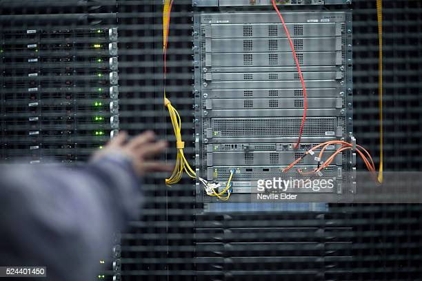 Elios Astudillo sales Engineer points out a server inside Index Exchange's cage at Equinix's Data transfer center in New Jersey High speed data...