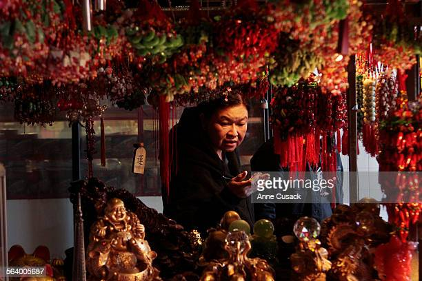 Elisa Aquino from Carson shops at a Kiosk owned by Stephani Yuan in Chinatown in Los Angeles Ca with her Filipino husband Manolo Aquino as they will...