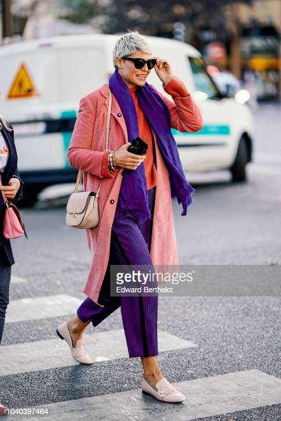 Elisa Nalin wears a pink jacket a purple scarf purple pants sunglasses outside Koche during Paris Fashion Week Womenswear Spring/Summer 2019 on...