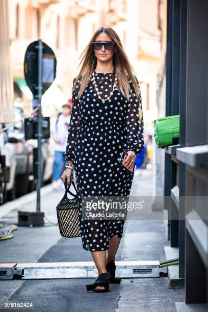 Elisa Taviti wearing black dress with white pois N21 shoes and Dior sunglasses is seen in the streets of Milan before the N21 show during Milan Men's...