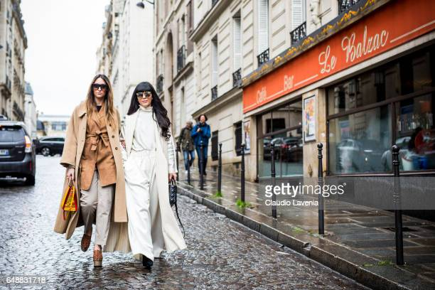 Elisa Taviti wearing Louboutin bag and Red Valentino shoes and trench and Laura Comolli are seen in the streets of Paris before the Giambattista...