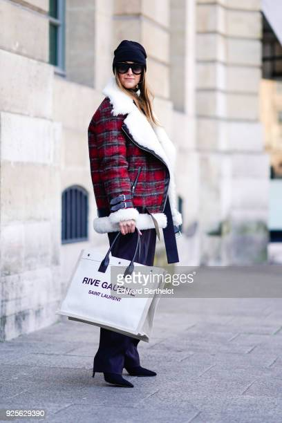 Elisa Taviti wears a black beanie hat a red checked pattern aviator jacket a Rive Gauche bag sunglasses suit pants during Paris Fashion Week...