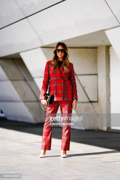 Elisa Taviti wears a red checked blazer jacket sunglasses suit pants a DG Dolce Gabbana bag outside Giambattista Valli during Paris Fashion Week...