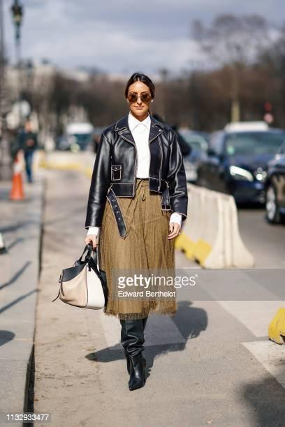 Elisa Taviti wears sunglasses, a black leather jacket, a white shirt, a bag, a khaki lace skirt, earrings, outside Paco Rabanne, during Paris Fashion...
