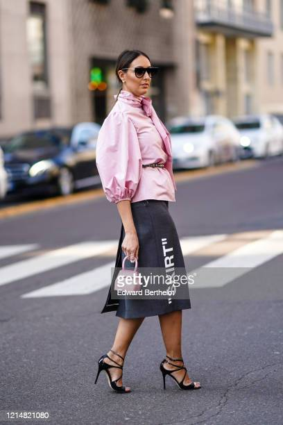 Elisa Taviti wears sunglasses, rings, earrings, a lustrous pink top with puff sleeves and a lavaliere, a lustrous pink small handbag, a dark grey...