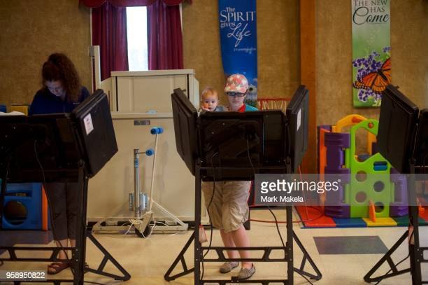 Elisabeth Ford holds her son Harrison 8 months while casting her vote at the Trucksville United Methodist Church polling station during the 2018...