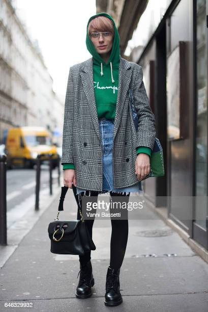Elisabeth Teixeira poses wearing a Champion sweater JW Anderson bag and Dr Martens boots before the Koche show at the Folies Bergere during Paris...