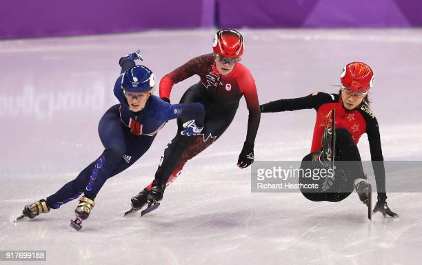 Elise Christie of Great Britain and Kim Boutin of Canada get past a falling Chunyu Qu of China during the Ladies' 500m Short Track Speed Skating...