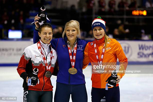Elise Christie of Great Britain celebrates her gold medal in the women's 500 meter with Jamie MacDonald of Canada who won the silver and Yara van...