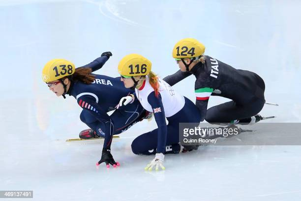 Elise Christie of Great Britain falls and collides with SeungHi Park of South Korea and Arianna Fontana of Italy as she competes in the Short Track...