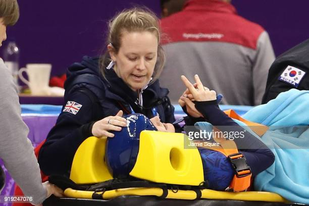 Elise Christie of Great Britain is carted off the ice on a stretcher after a crash with Jinyu Li of China during the Short Track Speed Skating...