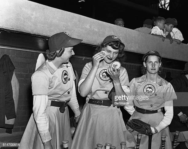 Elise Harney pitcher for the Kenosha Comets refreshes her makeup between innings as teammate Janice O'Hara and another player look on The women of...