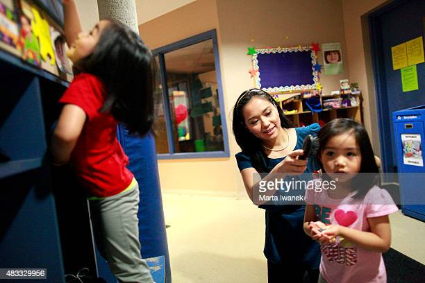 Elise HoFoong brushes daughter Sydney hair while Chloe plays to the left at TLC Daycare located in Markham Civic Centre in Markham