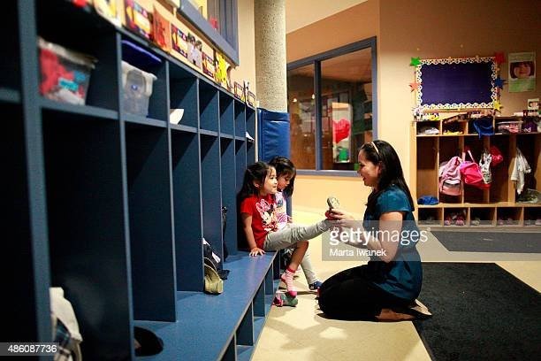 JULY 27 Elise HoFoong puts on daughter Chloe's shoe while twin sister Sydney waits beside her at TLC Daycare located in Markham Civic Centre in...