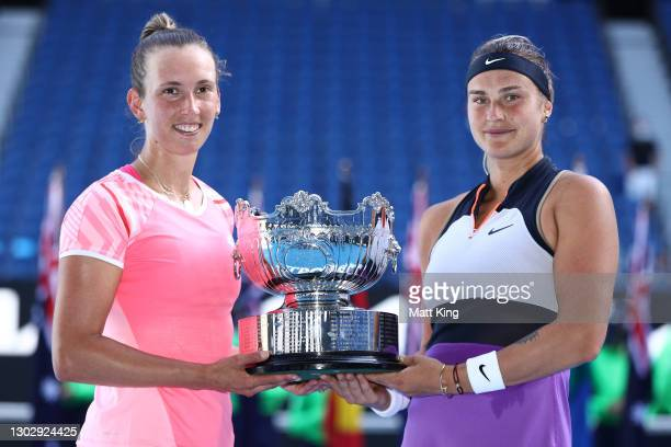 Elise Mertens of Belgium and Aryna Sabalenka of Belarus pose with the championship trophy after winning their Women's DoublesFinal match against...