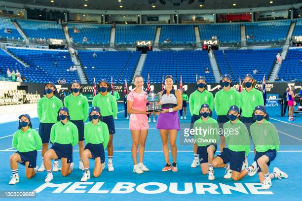 Elise Mertens of Belgium and Aryna Sabalenka of Belarus pose with the championship trophy and mask-wearing ball kids after winning their Women's...