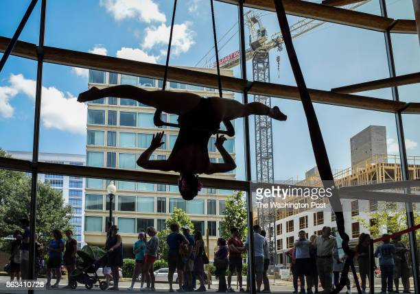 Elise Sipos an aerialist with the Trapeze School of New York dangles in the window in front of people lined up to get into the annual costume sale at...
