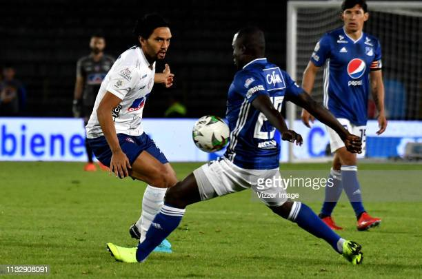 Eliser Quiñones of Millonarios vies for the ball with Abel Aguilar of Unión Magdalenaduring a match between Millonarios and Union Magdalena as part...