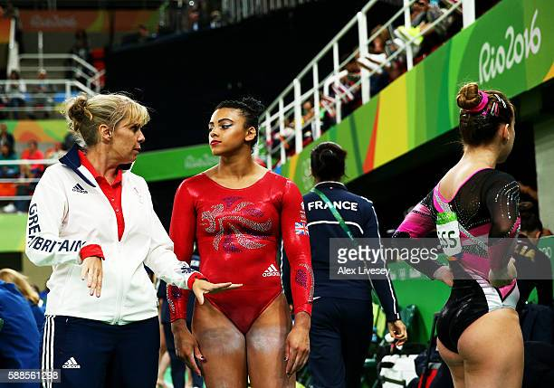 Elissa Downie of Great Britain listens to the instruction by her coach before competing on the balance beam during the Women's Individual All Around...