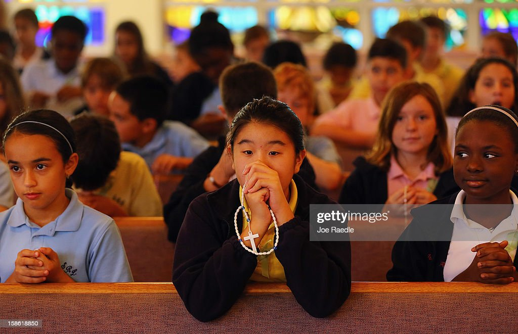 Elissa Irwanto prays during a service, at St. Rose of Lima School, for the victims of the school shooting one week ago in Newtown, Connecticut on December 21, 2012 in Miami, Florida. Across the country people marked the one week point since the shooting at Sandy Hook Elementary School in Newtown, Connecticut that killed 26 people.