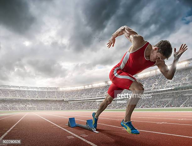 elite 100m runner sprints from blocks in floodlit stadium - athletics stock photos and pictures