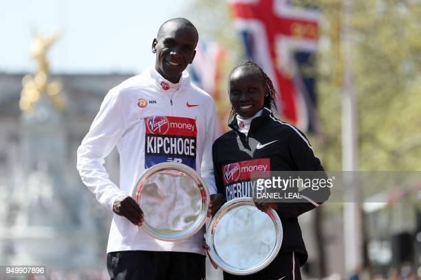 Elite men's race winner Kenya's Eliud Kipchoge and elite women's race winner Kenya's Vivian Cheruiyot pose during the trophy ceremony of the 2018...