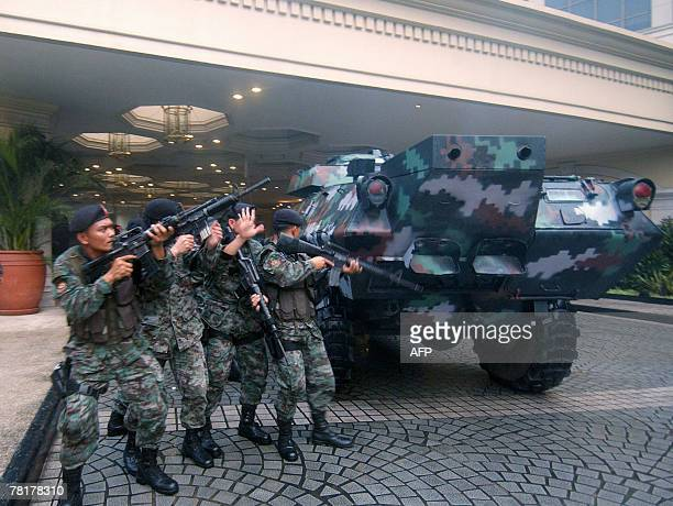 Elite police commandos begin an assault on the luxury Peninsula hotel in Manila's Makati financial district where rebel soldiers are holed up 29...