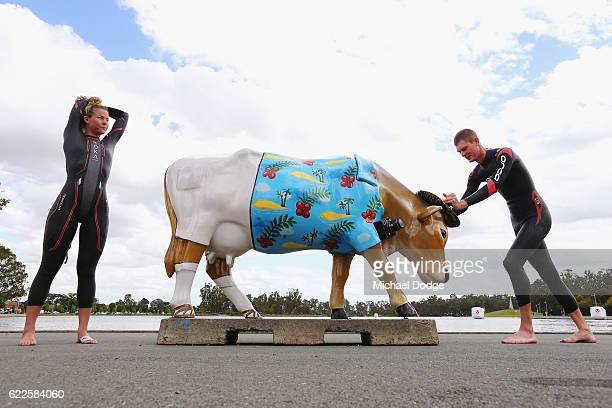 Elite triathletes Ellie Salthouse and Sam Betten stretch with an iconic cow statue at Victoria Lake before a training swim during Challenge...
