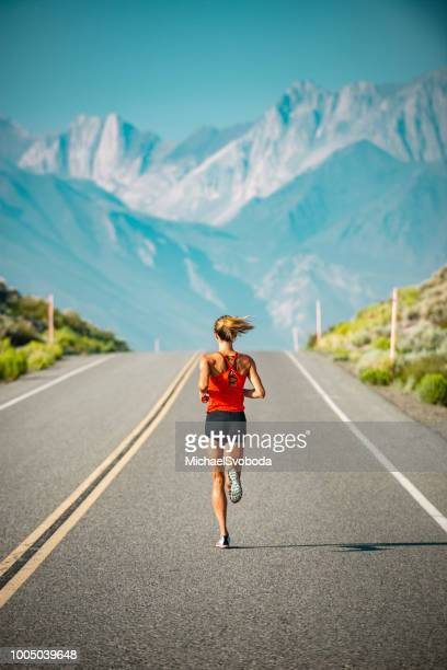 elite women athlete running up a road in the sierra mountains, california - forward athlete stock pictures, royalty-free photos & images